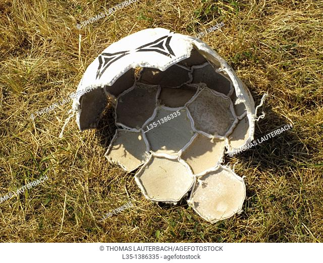 Old broken football on the lawn