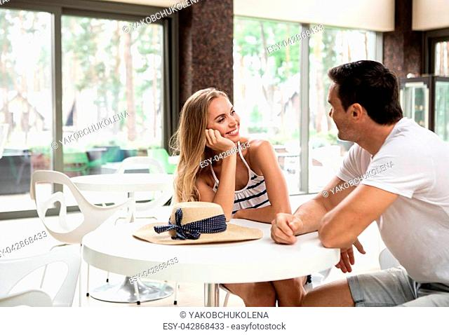 Side view of smiling man and woman sitting at table and talking. Cheerful female is looking at male with delight and tenderness