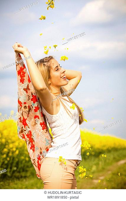 Young woman throwing colza flowers, Tuscany, Italy