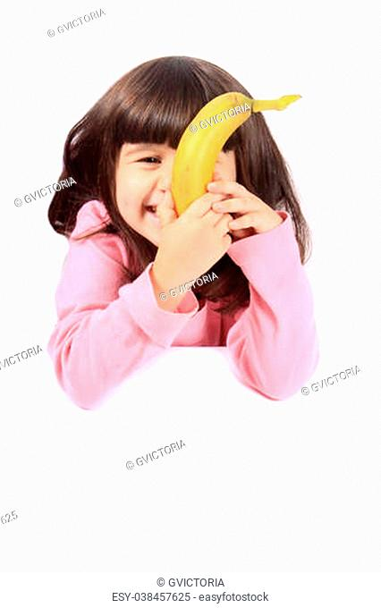 Young little girl hiding her face with a healthy banana while smiling