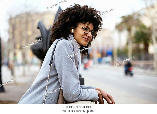 Spain, Barcelona, smiling woman with earphones in the city looking away