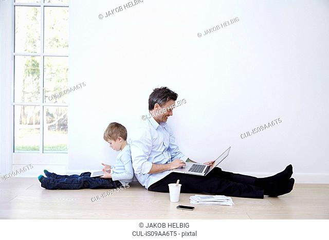 Father and son sitting back to back using laptop and digital tablet