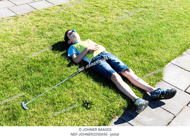 Boy on lawn with golf club and ball