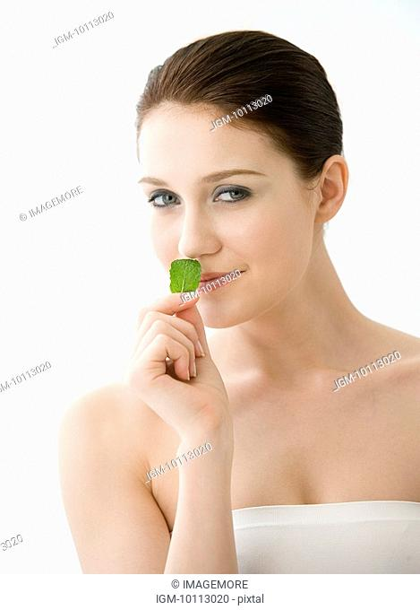 Close-up of young woman smelling herb and looking at the camera