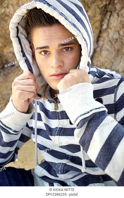 Portrait of a young man wearing a striped hood; Hawaii, United States of America