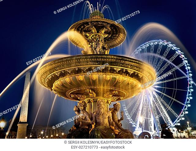 Fountain of Mars and ferris wheel on square of Concorde in evening Paris, France