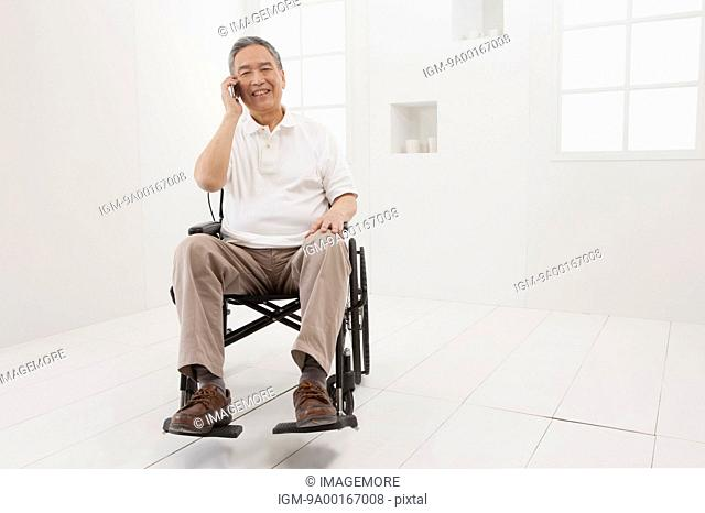 Senior man sitting on the wheel-chair and smiling