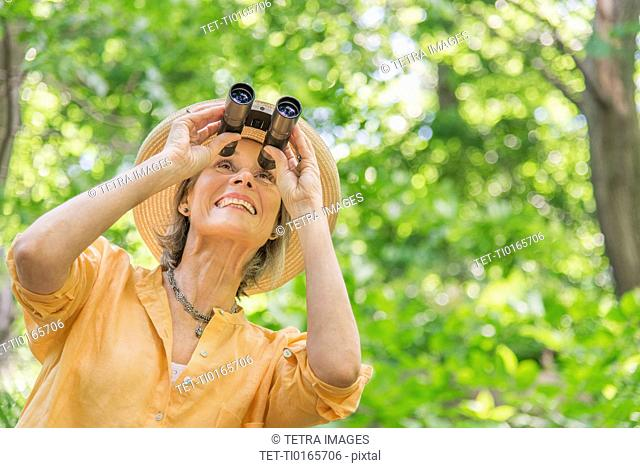 Senior woman with binoculars in park
