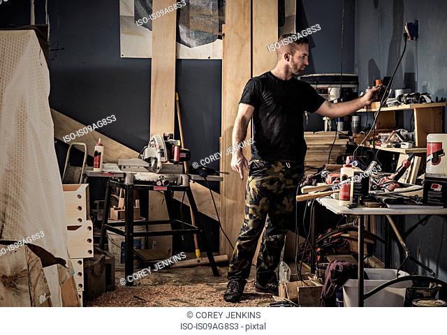 Male carpenter searching shelves in workshop