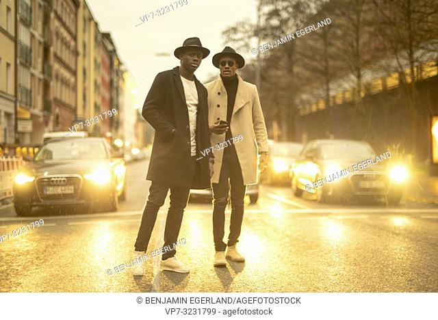 streetstyle, two men in the middle of the street in front of cars at night, lights, traffic, evening, Munich, Germany