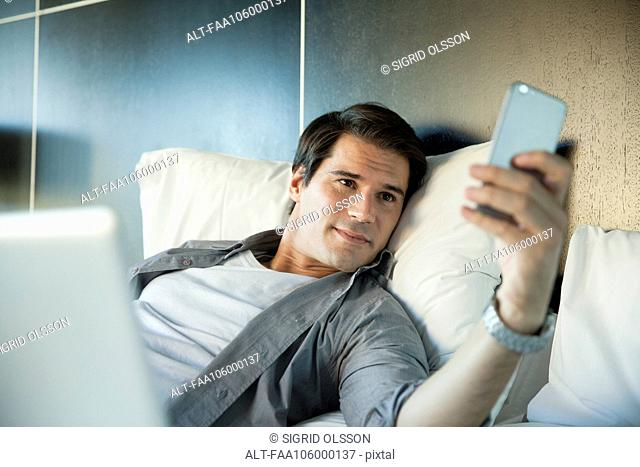 Man smiling at multimedia smartphone