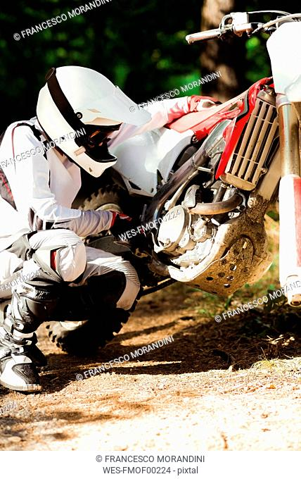 Italy, Motocross biker checking his bike