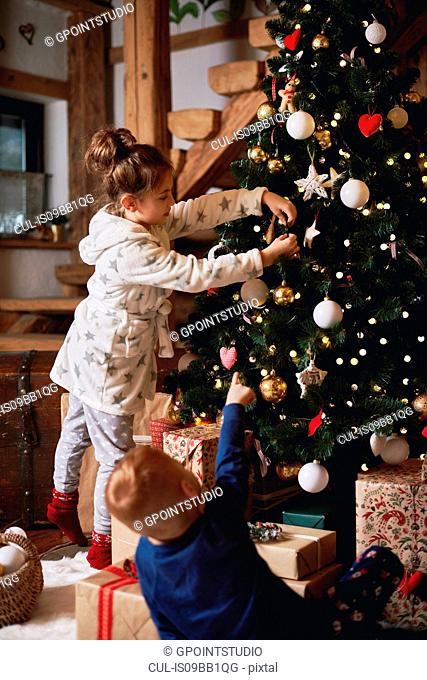 Young girl and boy decorating Christmas tree