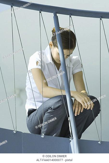 Female office worker crouching, head down, guard rail in foreground