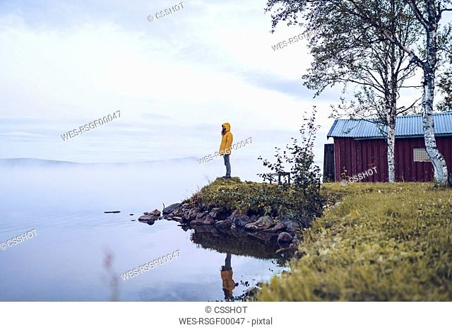 Sweden, Lapland, man wearing windbreaker standing at water's edge looking at distance