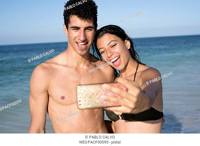Happy young couple taking selfies on the beach