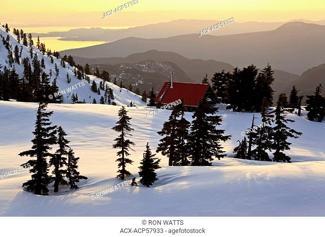 The sun sets on Mt. Steele cabin in Tetrahedron Provincial park on the Sunshine Coast with the Strait of Georgia and Vancouver Island as backdrop