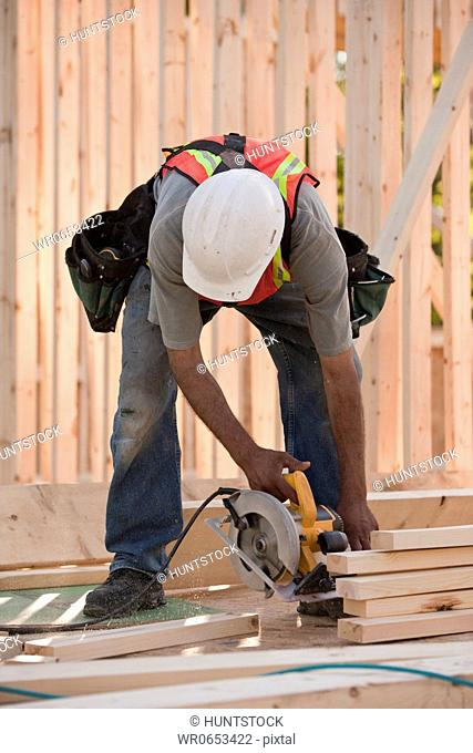 Carpenter sawing wood for house framing