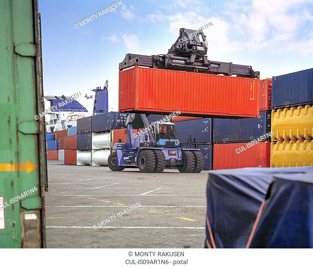 Stacker lifting shipping container in port, Grimsby, England, United Kingdom