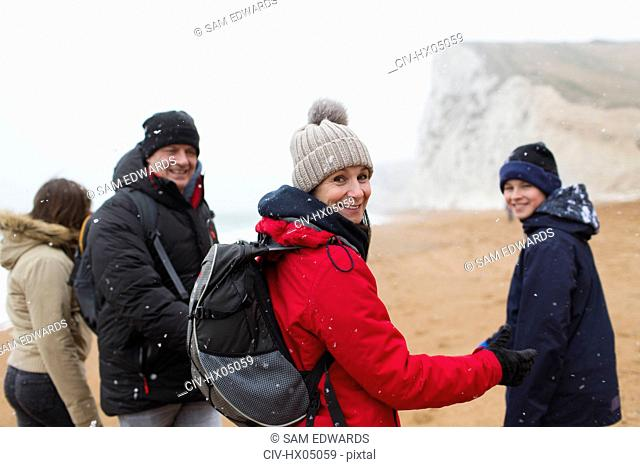 Portrait smiling family in warm clothing on snowy winter beach