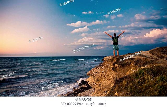 young man stands on the hill above the sea at sunset