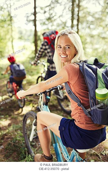 Portrait smiling mother with backpack mountain biking with family in woods