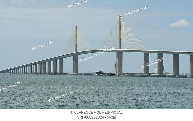 Traffic crosses the Sunshine Skyway Bridge over Tampa Bay as a tugboat pushes a barge underneath, as viewed from the south fishing pier