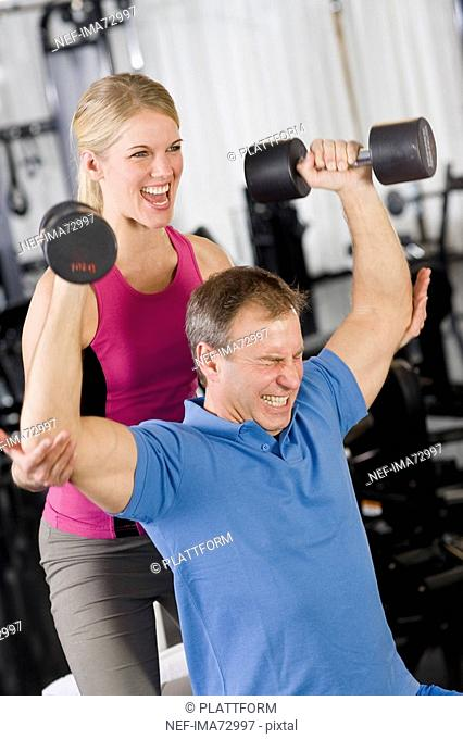 A man and a woman weight training at a gym Sweden