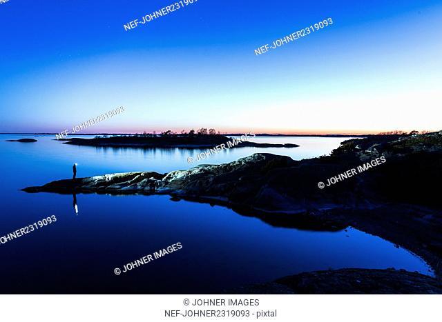 Man looking at lake at dawn