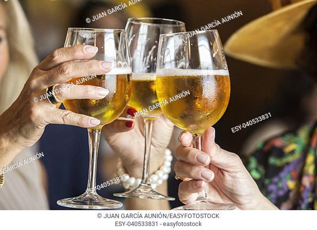 People at welcome cocktail party. Three mature women drinking a toast with glass chalice of beer. Selective focus