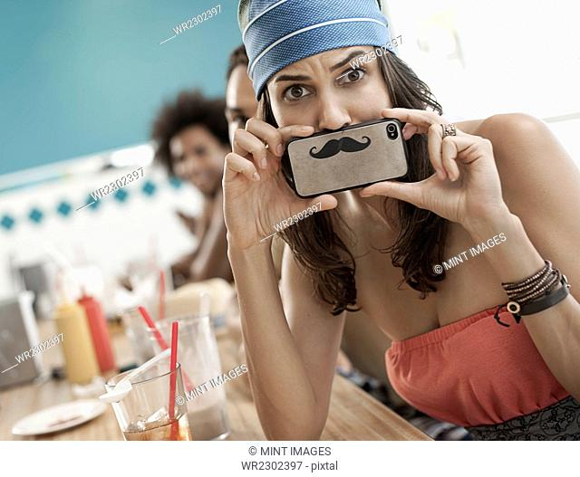 A woman holding a picture of a moustache on her smart phone just under her nose