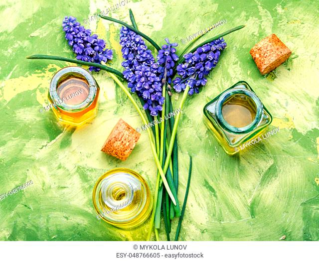 Lavender oil in glass bottle on a background of fresh flowers