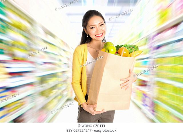 Young Asian woman hand holding shopping paper bag filled with groceries in market or department store