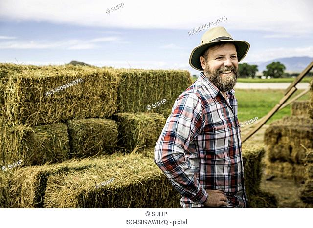 Mature man in front of hay bales, hands on hip looking away smiling