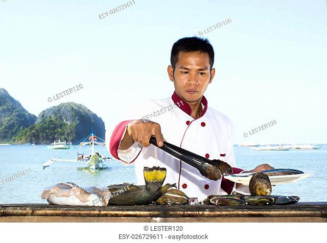 Filipino chef preparing a meal on the grill on the coast of El Nido