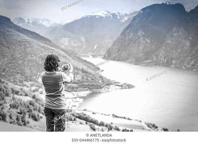 Tourism and travel. Woman tourist taking photo with camera, enjoying mountains fjords view in Sogn og Fjordane county. Norway Scandinavia, black and white photo