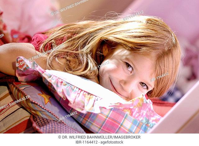 Little girls lying on pillows on her bed, smiling