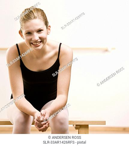 Dancer sitting on bench in studio