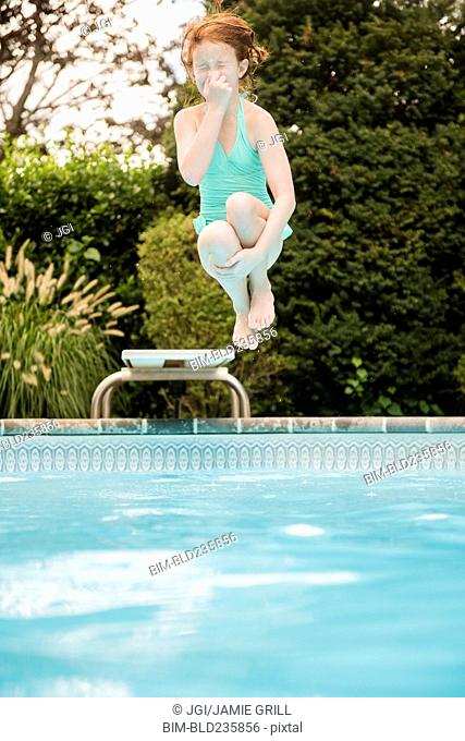 Caucasian girl holding nose jumping off diving board into swimming pool