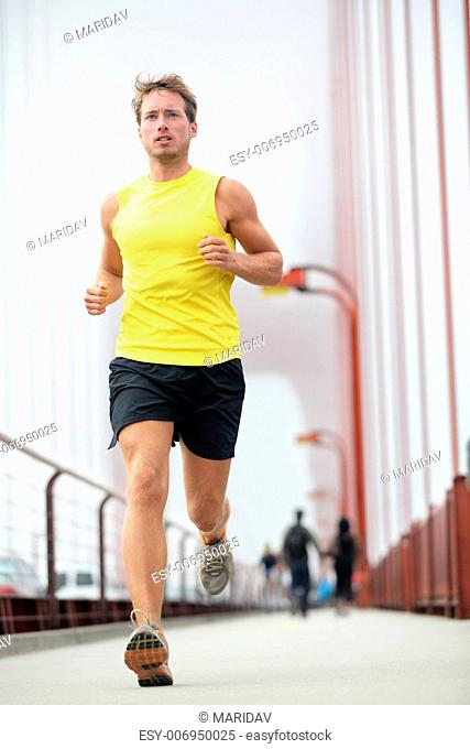Fit runner running outside. Young male fitness model training in yellow on Golden Gate Bridge, San Francisco, California, USA