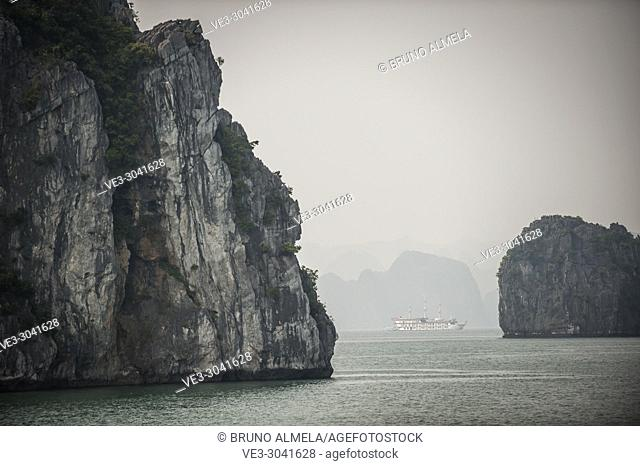 Tourists vessel between islands in the karst landscape of Ha Long Bay, Quang Ninh Province, Vietnam. Ha Long Bay is a UNESCO World Heritage Site