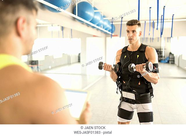 Man training with electrical muscle stimulation in gym monitored by man with tablet
