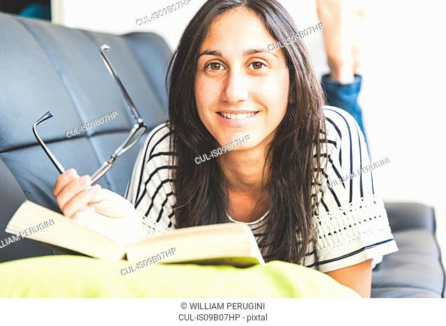 Woman lying on sofa with book looking at camera smiling
