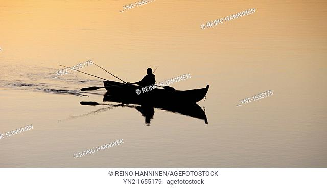 Fisherman trolling from a rowboat at sunset at river Oulujoki. Location Tuira Oulujoki Oulu Finland Scandinavia Europe