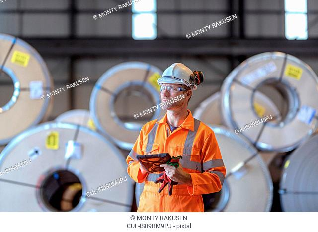 Portrait of worker using digital tablet by rows of sheet steel in storage at port