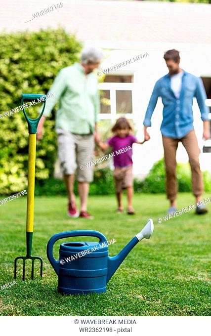 Rake and watering can with family walking in yard