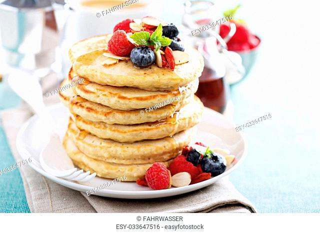 Fluffy oatmeal pancakes stack with fresh berries, coffee and syrup