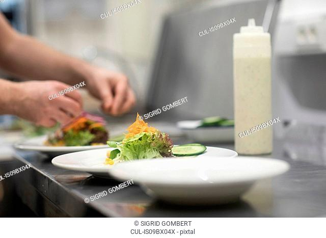 Fast food worker adding salad to hamburger in commercial kitchen, detail of hand