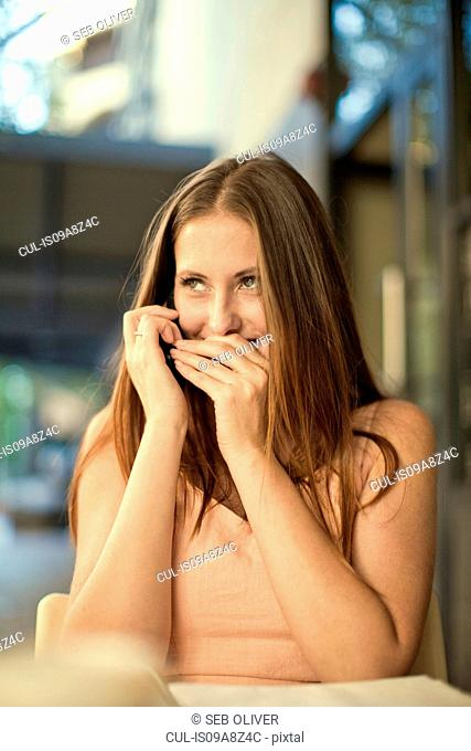 Young woman acting secretively in street cafe