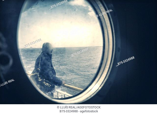 A man on the deck of a ship looking at the sea, seen through a window, Mediterranean Sea, Balearic Islands, Spain, Europe